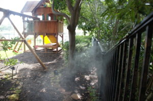 backyard with mosquito misting system spraying fence